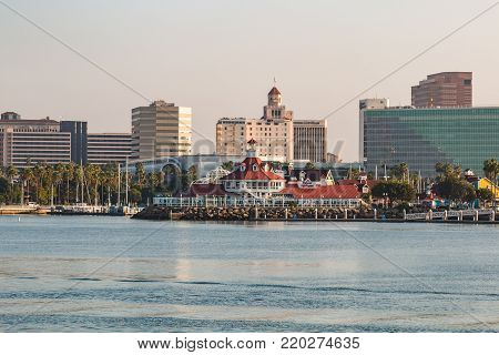 LONG BEACH, CALIFORNIA - SEPTEMBER 8, 2017:  Shops and restaurants line the shore of Long Beach Harbor, with a cityscape of downtown buildings.