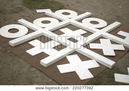 A life sized wooden tic tac toe boar game
