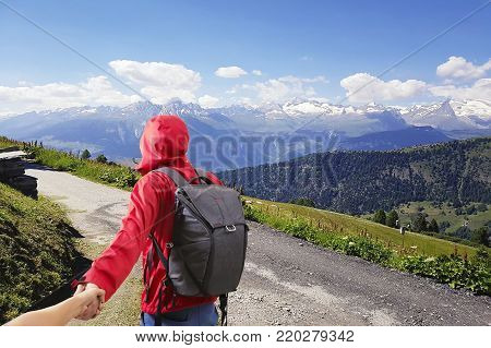 Couple summer vacation travel. Man walking on romantic honeymoon promenade holidays holding hand of wife following him at scenic summer mountains landscape.Tourism vacation and travel.