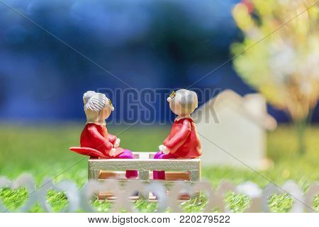 Old doll senior couple watching the night sky on green grass.Valentine's day.