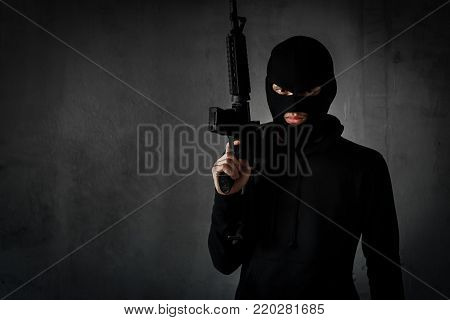 Robber,thieve or terrorist with gun and masked for  attack with assault rifle black suit ready shooting,aiming on copy space background violence concept