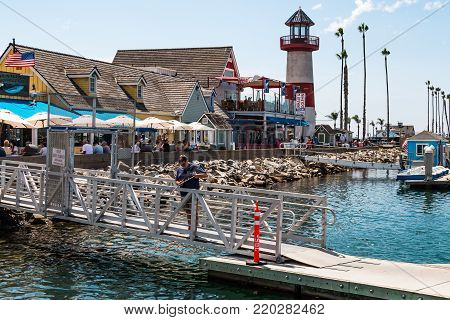 OCEANSIDE, CALIFORNIA - SEPTEMBER 9, 2017:  A man fishes at Oceanside Harbor Village, a popular tourist attraction for sportfishing, shopping and waterfront dining in San Diego County.