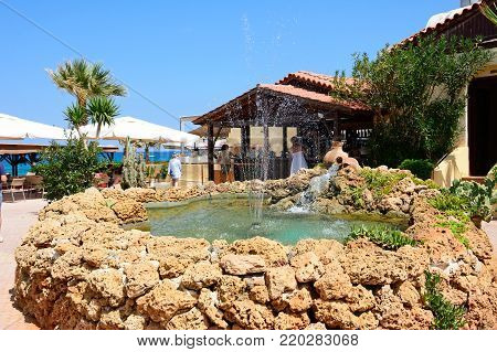 STALIDA, CRETE - SEPTEMBER 14, 2016 - Fountain in a small square surrounded by bars and restaurants with views towards the sea, Stalida, Crete, Europe, September 14, 2016.