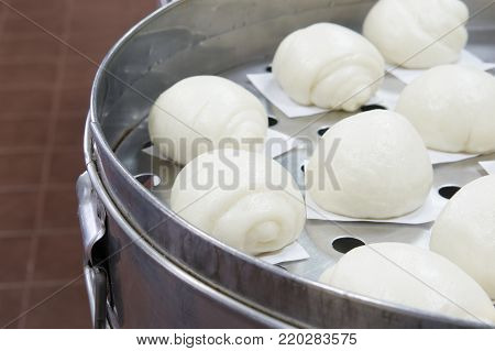 Close up steamed bun or dim sum on white paper in brown wooden tray have aluminium table as background at restaurant kitchen. Food and healthy concept photography.