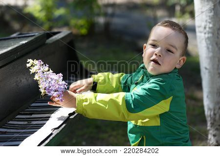City Gomel, Belarus.May 17, 2017 Gomel kindergarten, graduation day.Cheerful boy sings a song for a paper piano.Teaching your child music.Play the piano and sing songs