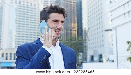Businessman talk to cellphone over cityscape background, serious talking, replying customer