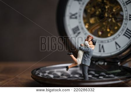 Miniature happiness couple standing on vintage pocket watch, husband holding his wife celebrate valentines'day or forever love concept.