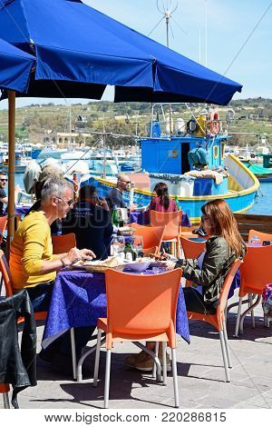 MARSAXLOKK, MALTA - APRIL 1, 2017 - Tourists relaxing at a pavement cafes along the waterfront with traditional Maltese fishing boats in the harbour to the rear, Marsaxlokk, Malta, Europe, April 1, 2017.