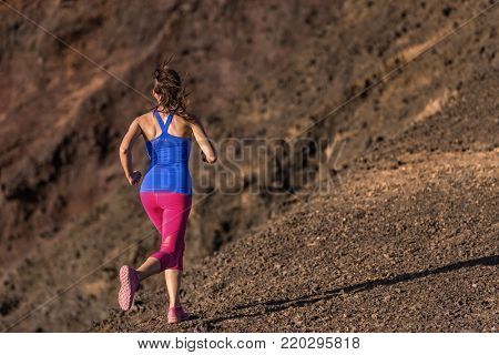 Woman running outside to lose weight, cellulite fat burning concept. Female runner girl training body for weight loss during summer outdoor workout. Sport lifestyle.