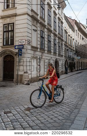 Vienna,  Austria - August 16, 2017: Unidentifies woman cyclist in jewry district in historical city center of Vienna