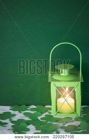 Lit green lamp surrounded by shamrocks - St Patrick greeting card idea with a green lamp with a lit candle inside, surrounded by green paper clovers, on a green wooden background.