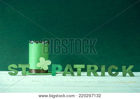 St Patrick words and a leprechaun hat - Green leprechaun paper hat with a shamrock and the words St Patrick written in green wooden letters, on a wooden background with space for text.
