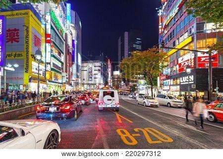 TOKYO, JAPAN - NOVEMBER 12, 2016: Cars in traffic at Shibuya district in Tokyo, Japan. Shibuya road cross is one of the busiest crosswalks in the world.