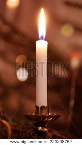 close photo of a Christmas candle on the tree in redish tones