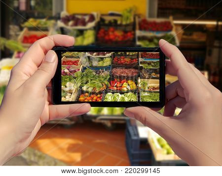 Female taking picture of variety fresh vegetables for sale in a market in Italy on smart phone. Picture of fresh vegetables in the box in mobile phone