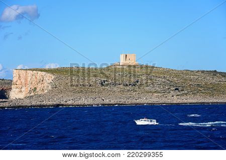 COMINO, MALTA - APRIL 3, 2017 - View of the island with a small boat in the foreground during the Springtime, Comino, Malta, Europe, April 3, 2017.