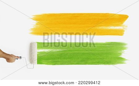hand with paint roller painting color orange and green, close up  isolated on blank white wall background