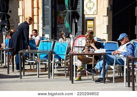 MOSTA, MALTA - APRIL 2, 2017 - Tourists relaxing at a pavement cafe in the town centre, Mosta, Malta, Europe, April 2, 2017.