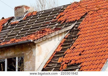 the roof of the old house with a damaged coating of red ceramic tiles