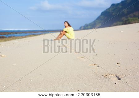 Footprints on the white sand on the right side of the picture. Unfocused girl in the yellow dress sitting on the beach. Ocean coast and blue sky in the background
