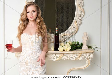 Elegant blonde lady with glass of wine. Beautiful sexy young woman with long hair perfect body and pretty face make-up in evening dress drinking alcohol in light luxury interior.