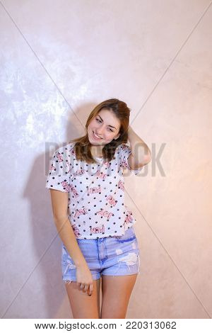 Cute young woman smiles beautifully and in high spirits looks and poses, changing poses to camera in bright silvery confetti, standing against background of light wall in room. European-looking girl with red hair dressed in bright T-shirt and short denim