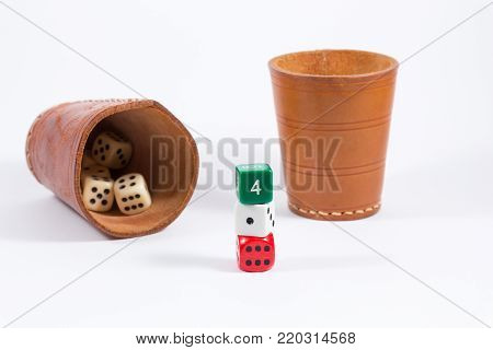 two brown leather cups filled with dice and three white red green colored dice stacked on top of each other showing four one six isolated on white background