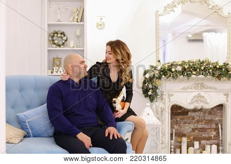 Beautiful spouses, loving husband and wife smile and look at camera, pose and hug each other, sitting on soft blue couch in bright living room with fireplace decorated in festive. Woman of European appearance with long curly blond hair dressed in beautifu