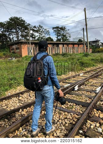 Dalat, Vietnam - Dec 3, 2017. A photographer with backpack walking on old rail tracks in Dalat, Vietnam. Da Lat was developed as a resort by the French in the early 1900s.
