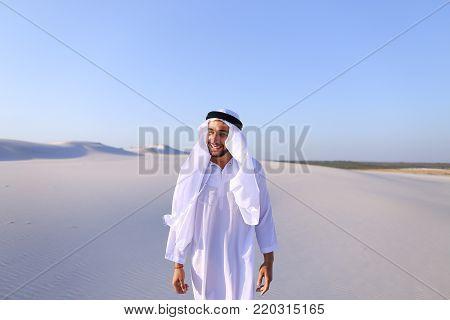 Cheerful Muslim guy walks along white sand of wide desert on warm summer evening. Swarthy, handsome Muslim with short dark hair dressed in kandura,