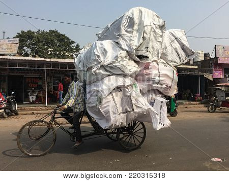 Agra, India - Nov 5, 2017. Hard working young man carries heavy bags of cargo in Agra, India. Agra is one of the most populous cities in Uttar Pradesh, and the 24th most populous in India.