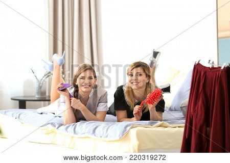 Young chambermaids in uniform resting on bed indoors