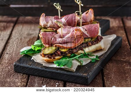 Delicius sandwiches with smoked pork, cucumbers and onion on a black wooden board.
