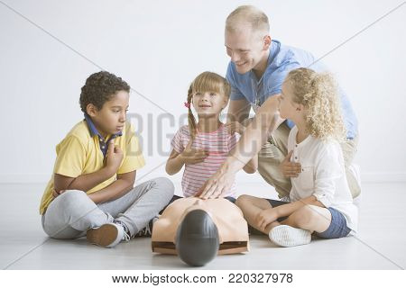 Young paramedic during first aid procedures demonstration lesson for children poster