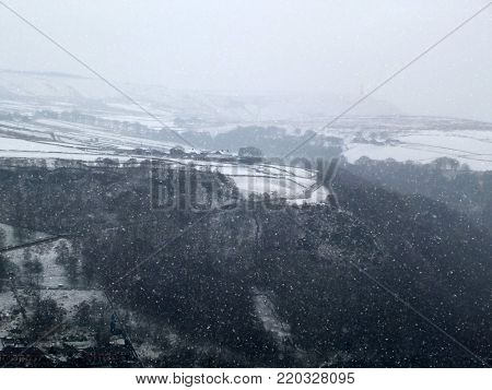 snow falling in a yorkshire pennine landscape with stoodley pike in the distance