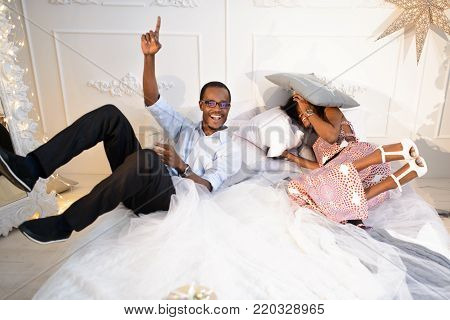 The happy loving afro-american couple is getting crazy on the Christmas eve near the New Year tree, they are lying on the bed ang laughing a lot.