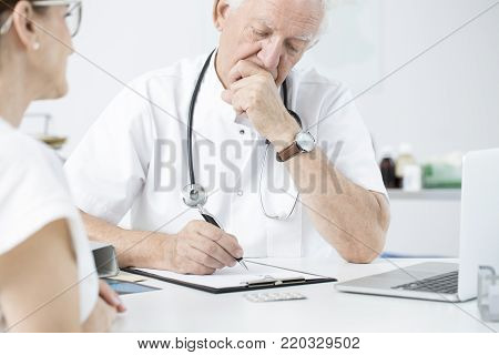 Surgeon in white uniform giving expert opinion before the patient's surgery