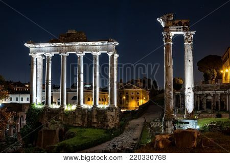 Night view to temple of Saturn and temple of Vespasian and Titus in Forum Romanum, Rome. Copy space in night sky.