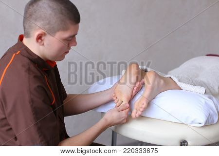 Sociable and professional man doctor actively rubs feet and conducts medical procedure, talking with female patient who lies on couch in light cosmetic salon. Man of European appearance with short haircut dressed in brown medical uniform from shirt and pa