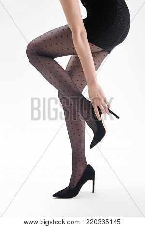 Shapely female legs in black tights and high heels.