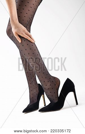 Tired, aching legs in high heels. Shapely female legs in black tights and high heels.