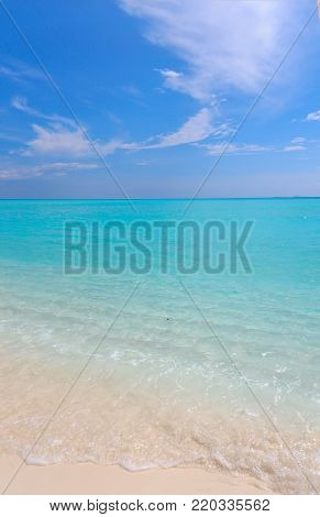 Peaceful white sandy beach with clear water of blue ocean lagoon. Concept: peace, tranquility, serenity, tropical vacations,carefree
