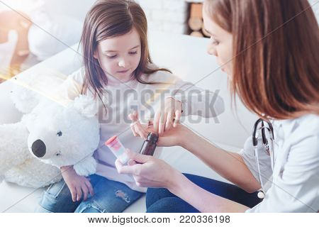 Let me take it. Attentive kid sitting on her sofa and hugging her bear while looking at medicine