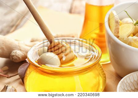 Glass jar with honey and garlic as natural cold remedies on table, closeup