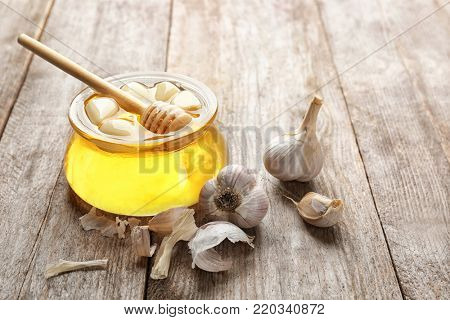Glass jar with honey and garlic as natural cold remedies on wooden background