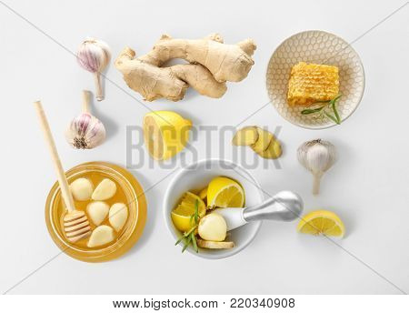 Composition with honey and garlic as natural cold remedies on white background, top view