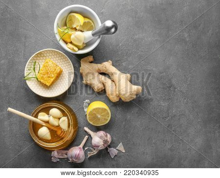 Composition with honey and garlic as natural cold remedies on grey textured background, top view
