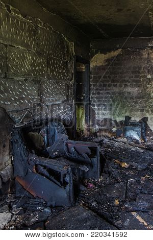 Burnt apartment house interior. Burned chair, charred walls.