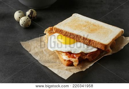 Tasty toast with fried egg and bacon on table