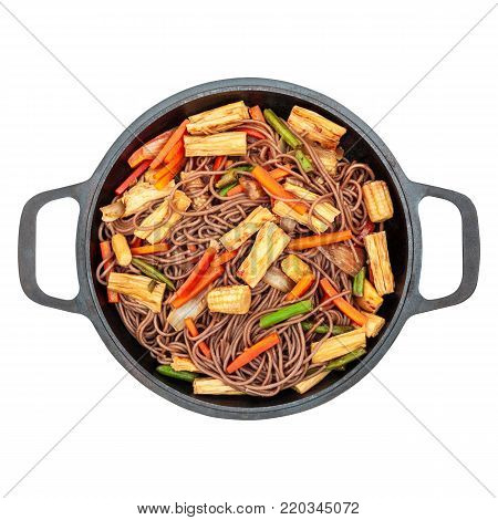 Delicious buckwheat noodles with tofu skin and vegetables in a cast iron wok isolated on white background closeup